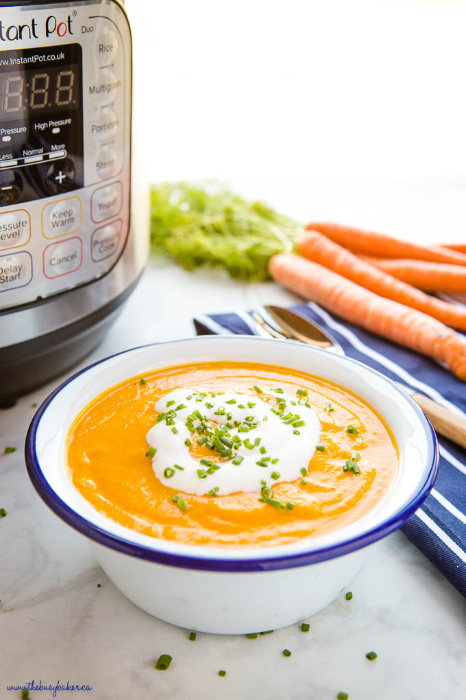 bowl of carrot ginger soup with coconut cream and chives