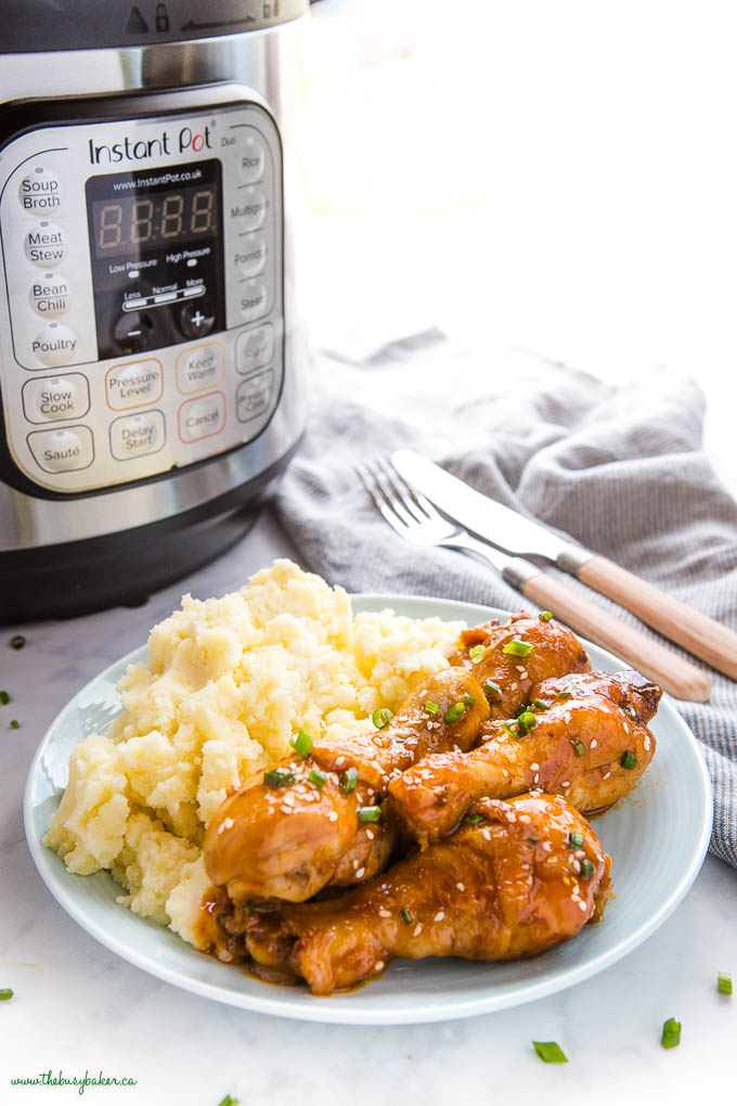 chicken drumsticks with honey garlic sauce on blue plate with mashed potatoes