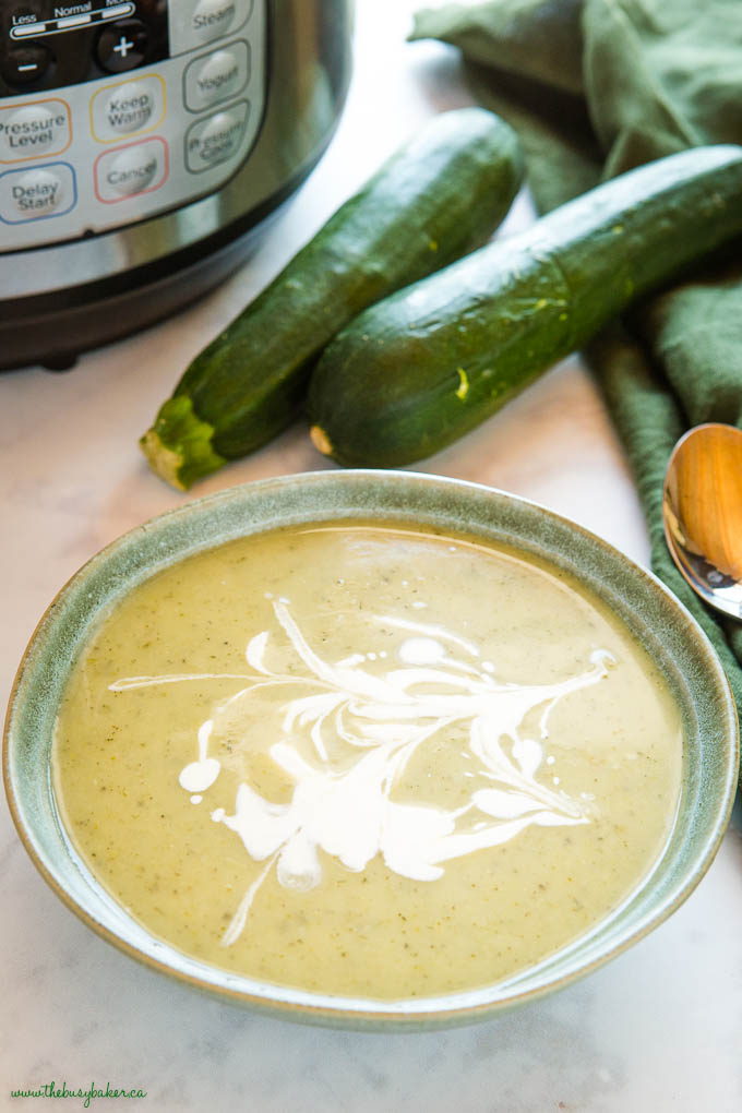 green bowl with zucchini soup and cream