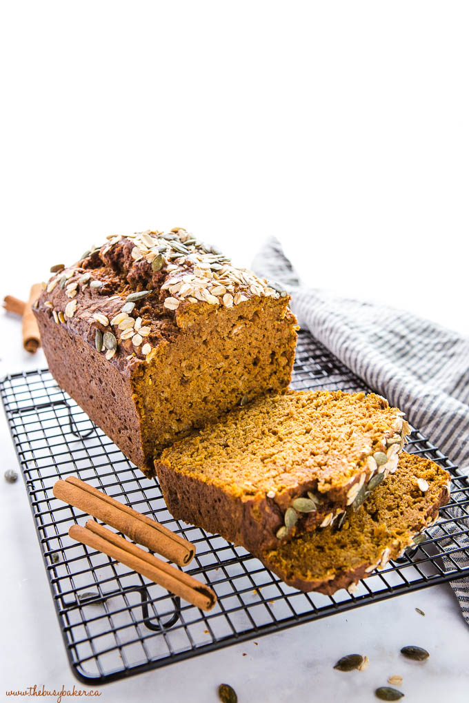 pumpkin oat bread on black wire rack with oats and cinnamon