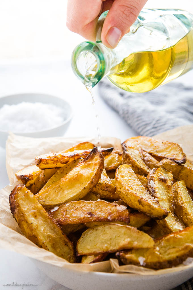 hand pouring vinegar from a recycled glass bottle, over crispy potato wedges with flaky sea salt