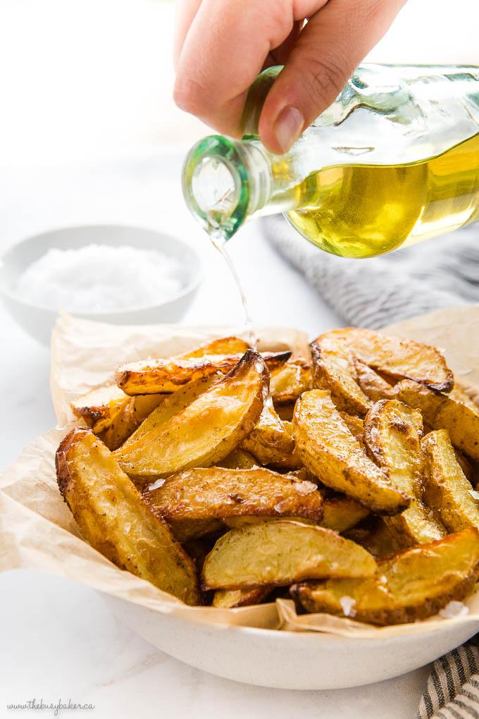 hand pouring vinegar over crispy potato wedges
