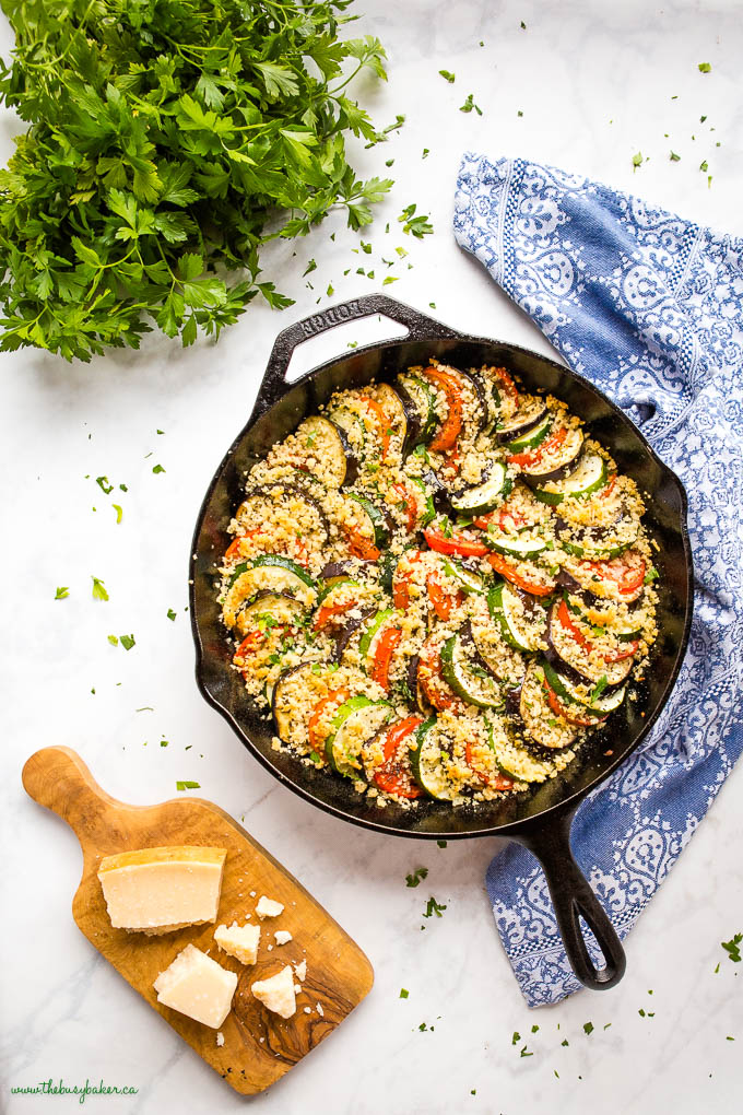 overhead image: sliced veggie gratin in cast iron skillet with parmesan cheese