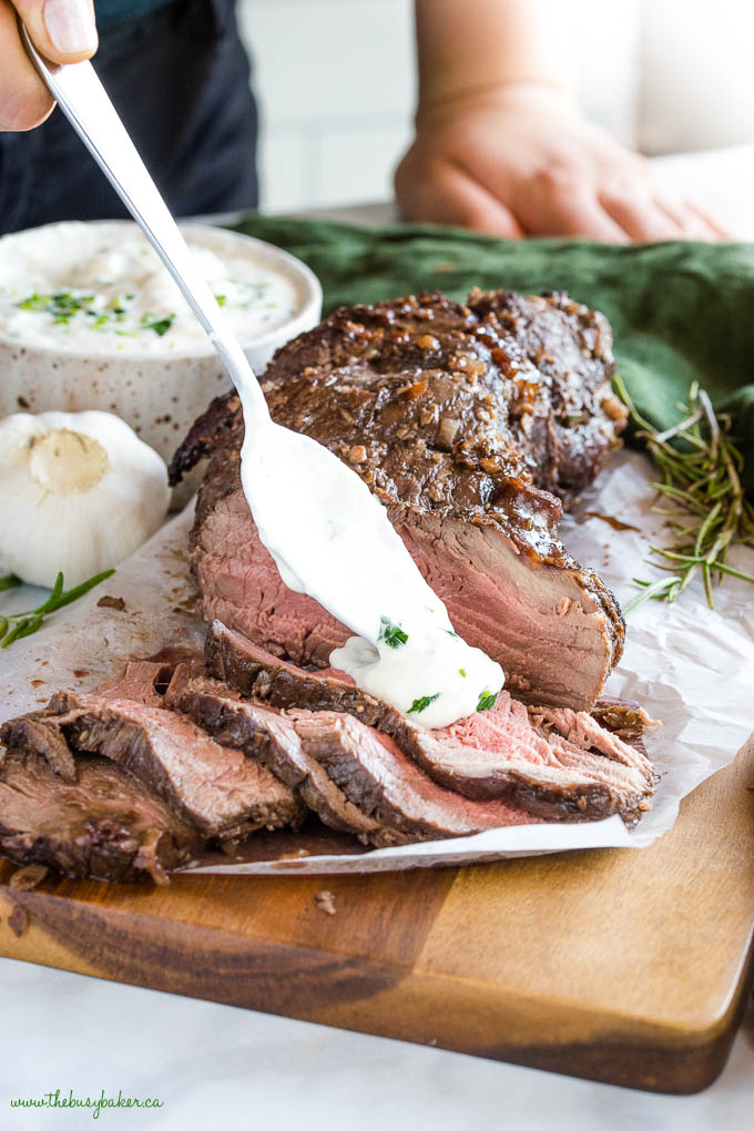 sliced beef tenderloin with a spoonful of creamy horseradish sauce