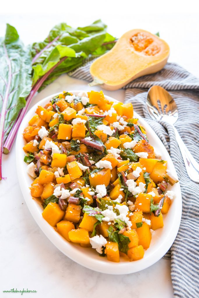 white platter with caramelized butternut squash, greens, and goat cheese