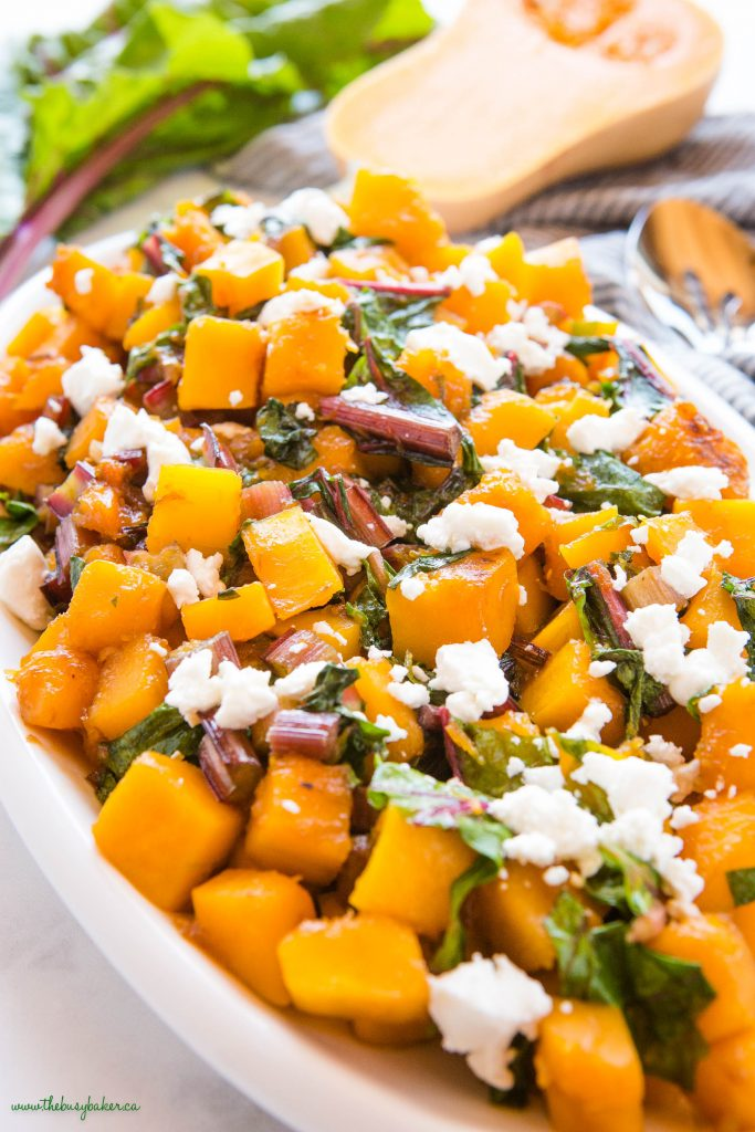 close-up image: caramelized butternut squash with greens and goat cheese on a white platter