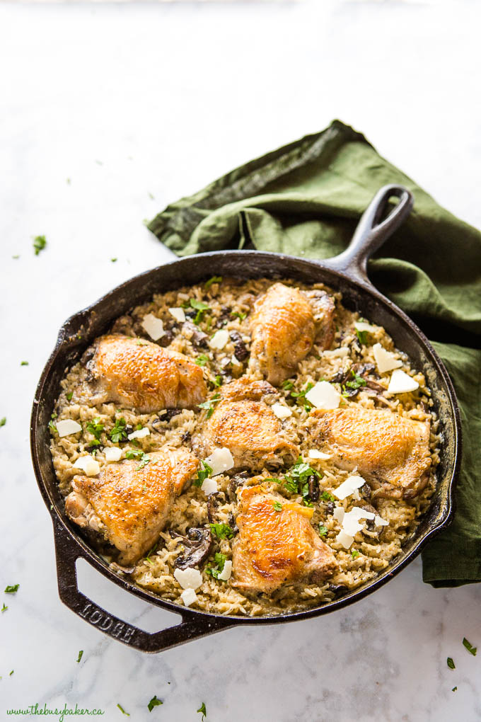 large cast iron pan with creamy mushroom rice and chicken thighs