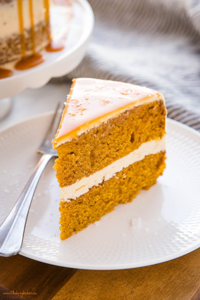 slice of pumpkin cake with salted caramel sauce on top, on white plate with fork