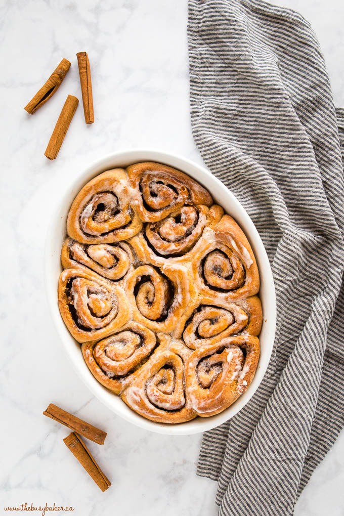 overhead image: glazed whole wheat cinnamon rolls in a white baking dish with a striped kitchen towel and cinnamon sticks
