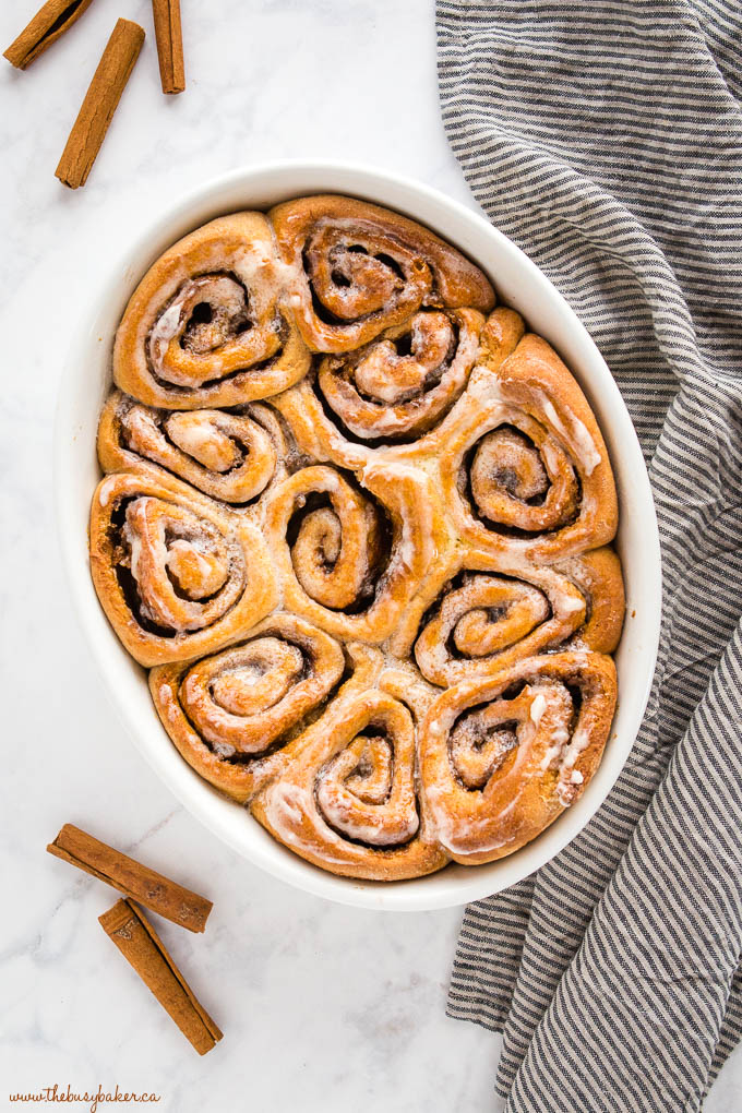 overhead image: oval baking dish with whole wheat cinnamon rolls with a simple glaze