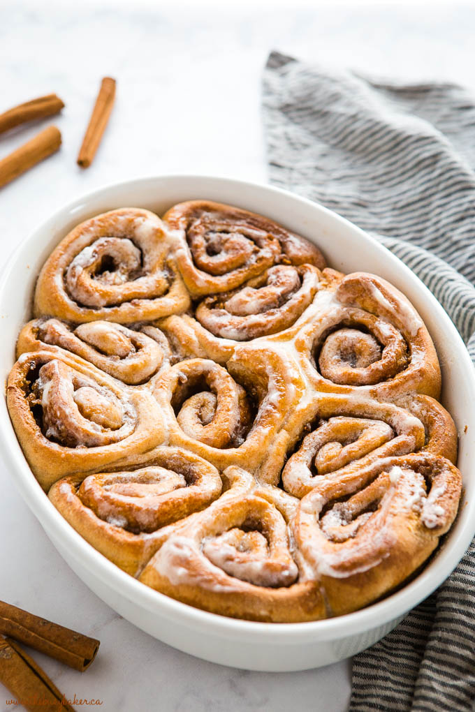 whole wheat cinnamon rolls baked in a white oval baking dish with glaze