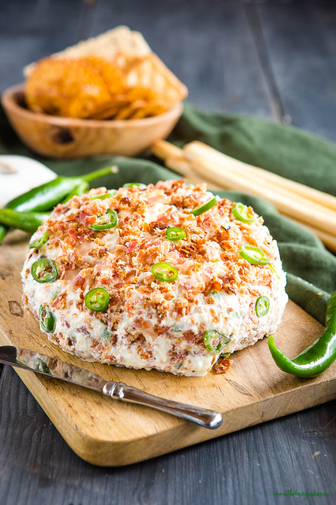 Bacon Ranch Jalapeno Cheese Ball on a wooden board with a cheese knife