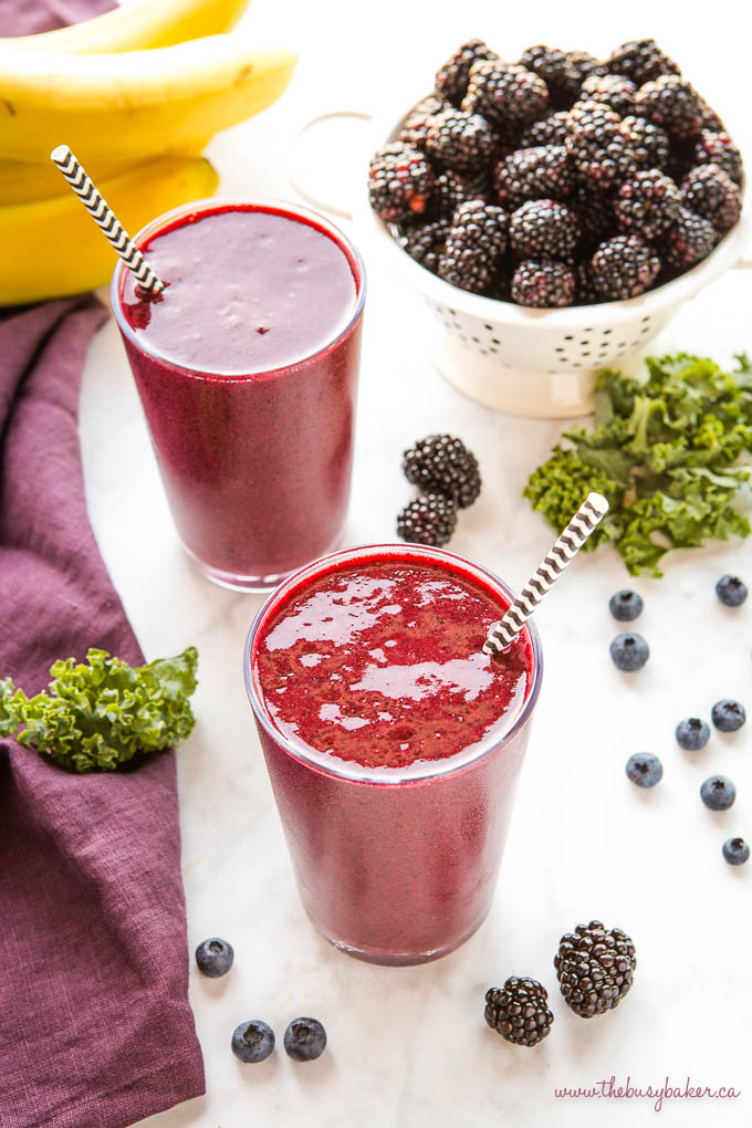 2 blackberry kale smoothies with paper straws