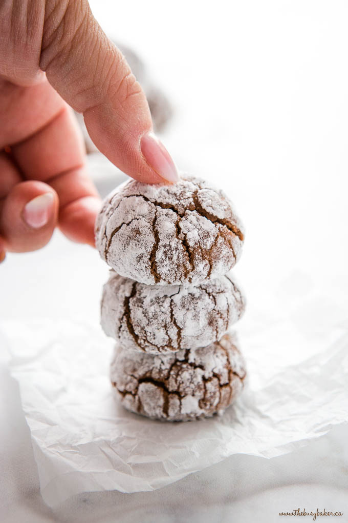 a hand reaching for a chocolate crinkle cookie