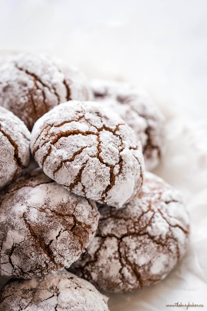 pile of holiday chocolate crinkle cookies with white powdered sugar