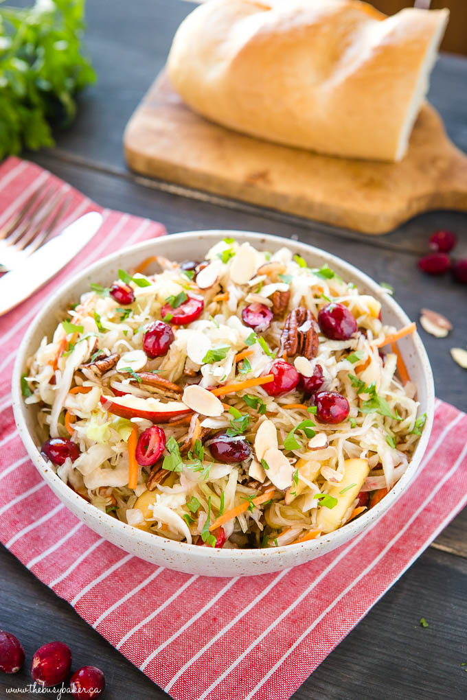 maple cranberry coleslaw in ceramic bowl with cabbage, carrots, cranberries and nuts