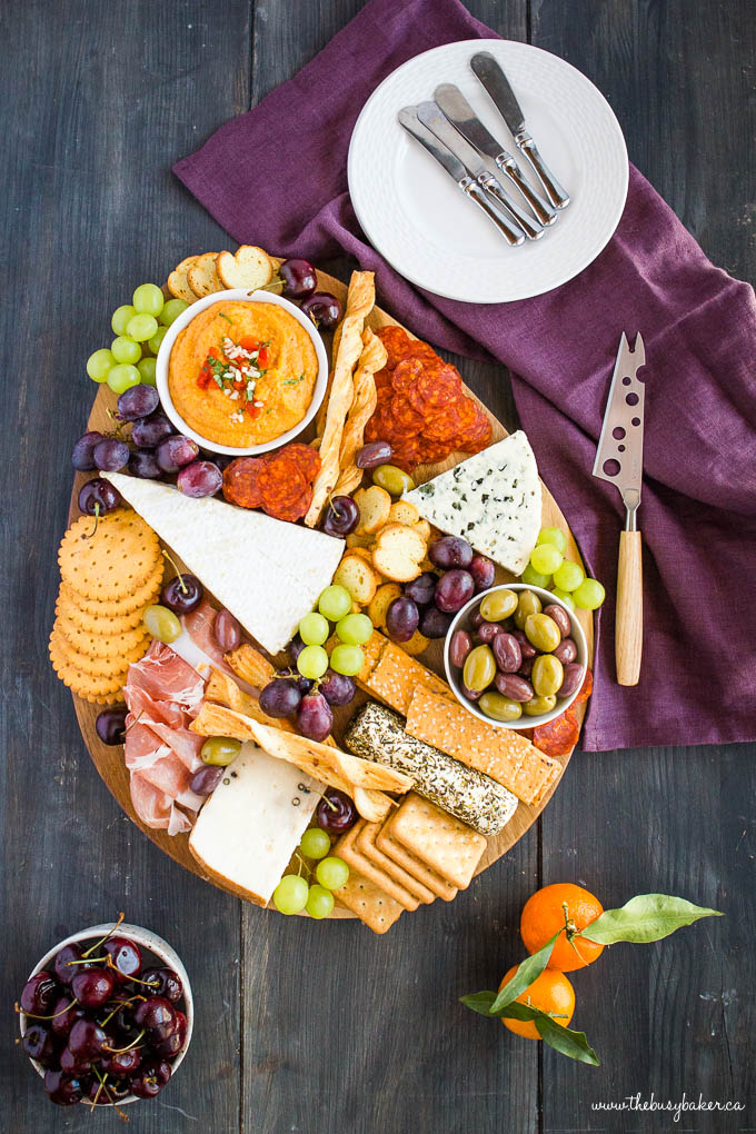 overhead image: charcuterie board with grapes, cherries, meats and cheeses