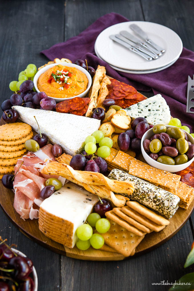 charcuterie board with meat, cheese, crackers, and fruit