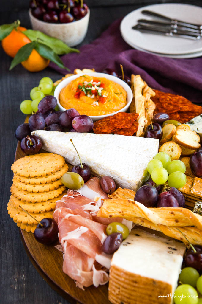 charcuterie board with meats, cheeses, olives, and fruit