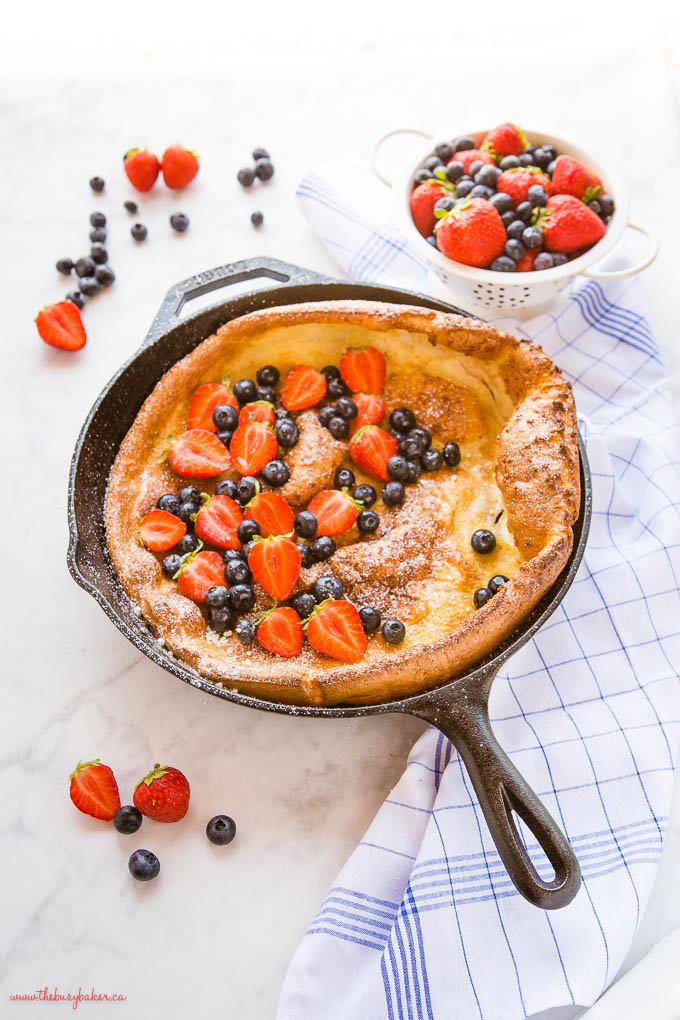 skillet pancake with fresh berries and powdered sugar