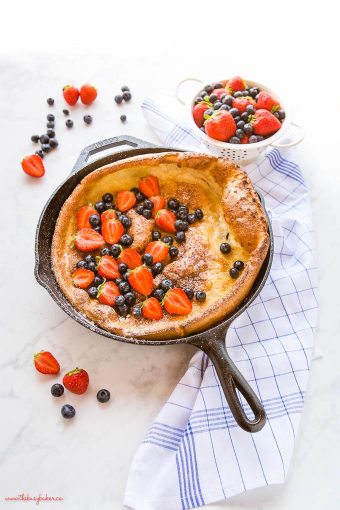 Dutch baby pancake in skillet with fresh berries