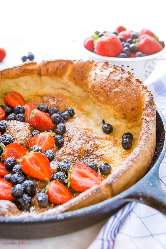 the crispy edge of a dutch baby pancake with berries and powdered sugar