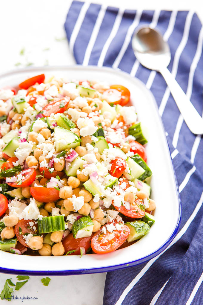 Greek salad with chickpeas, feta cheese and red onions in white enamel dish