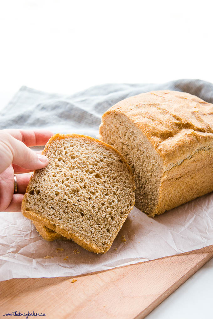 hand reaching for a slice of whole wheat bread
