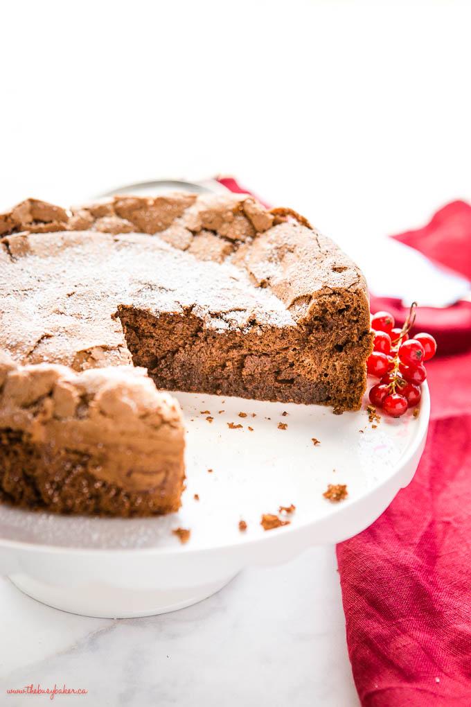 flourless chocolate cake on white cake stand