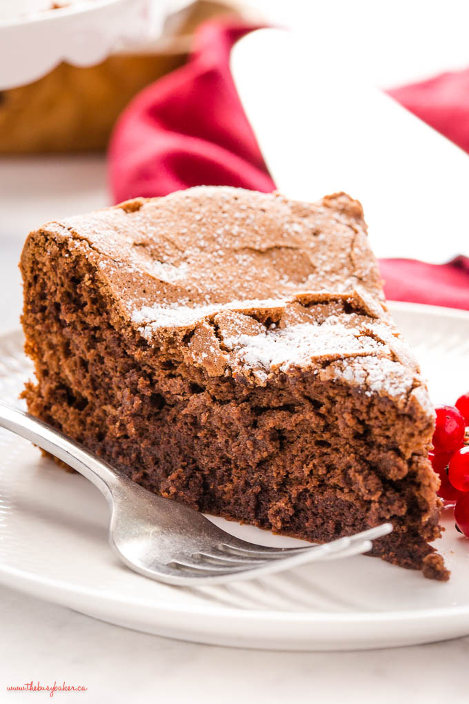 slice of fudgy flourless chocolate cake on white plate with a fork