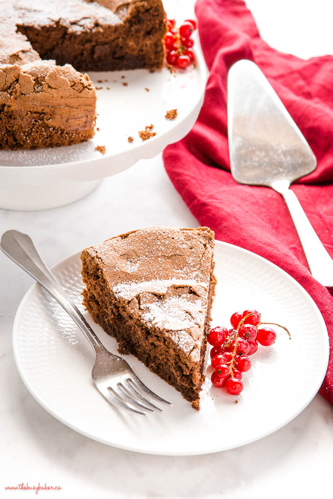 slice of flourless chocolate cake on white plate with red berries