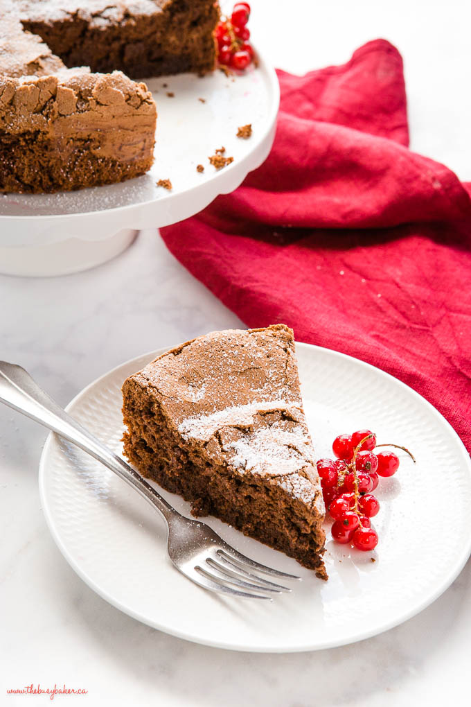 slice of flourless chocolate cake with red currants on a white plate