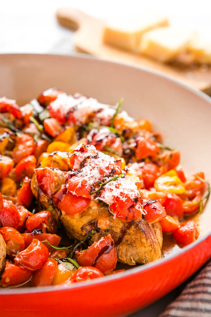 closeup image: chicken breasts with chopped tomatoes, balsamic and parmesan