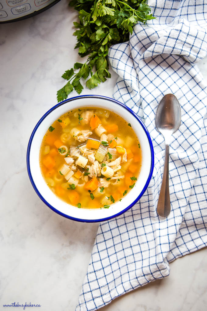 overhead image: Instant Pot Chicken Noodle Soup in white bowl with blue rim