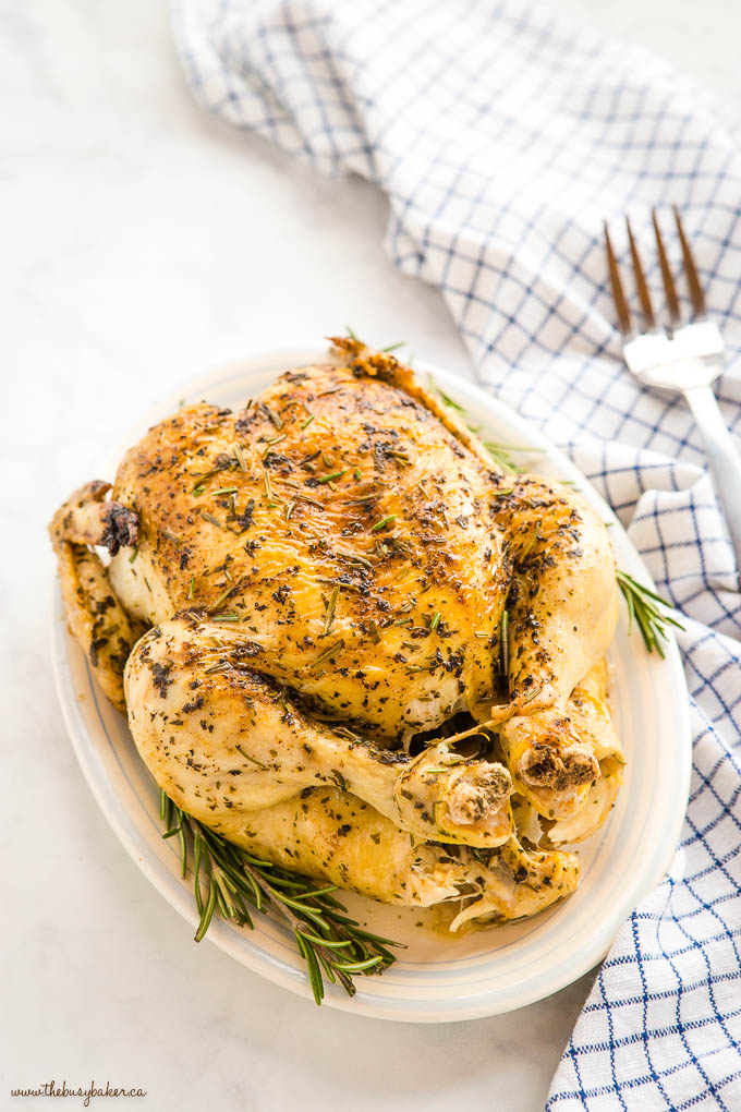 roast chicken on white platter with fresh rosemary and serving fork