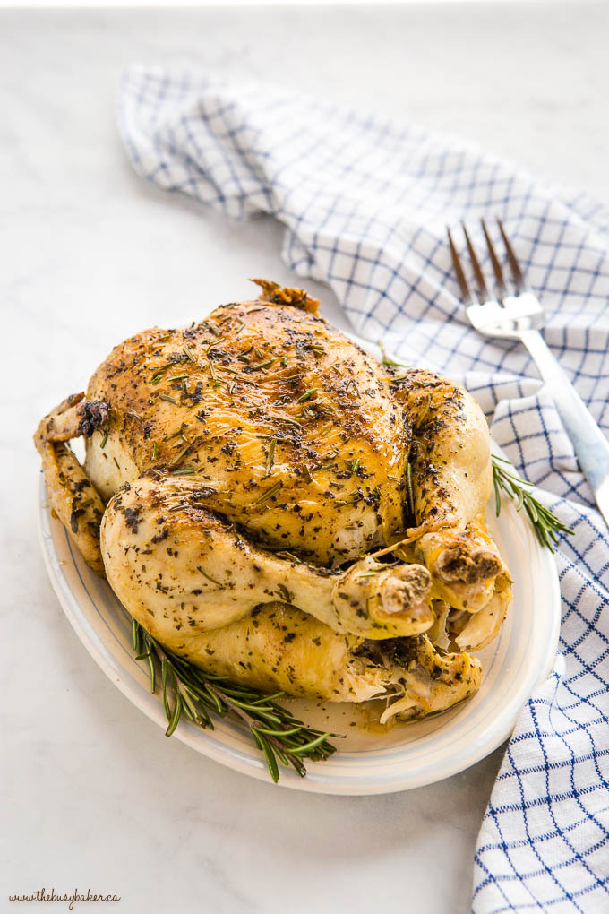 Roasted Chicken with Crispy Skin on white plate with fresh rosemary