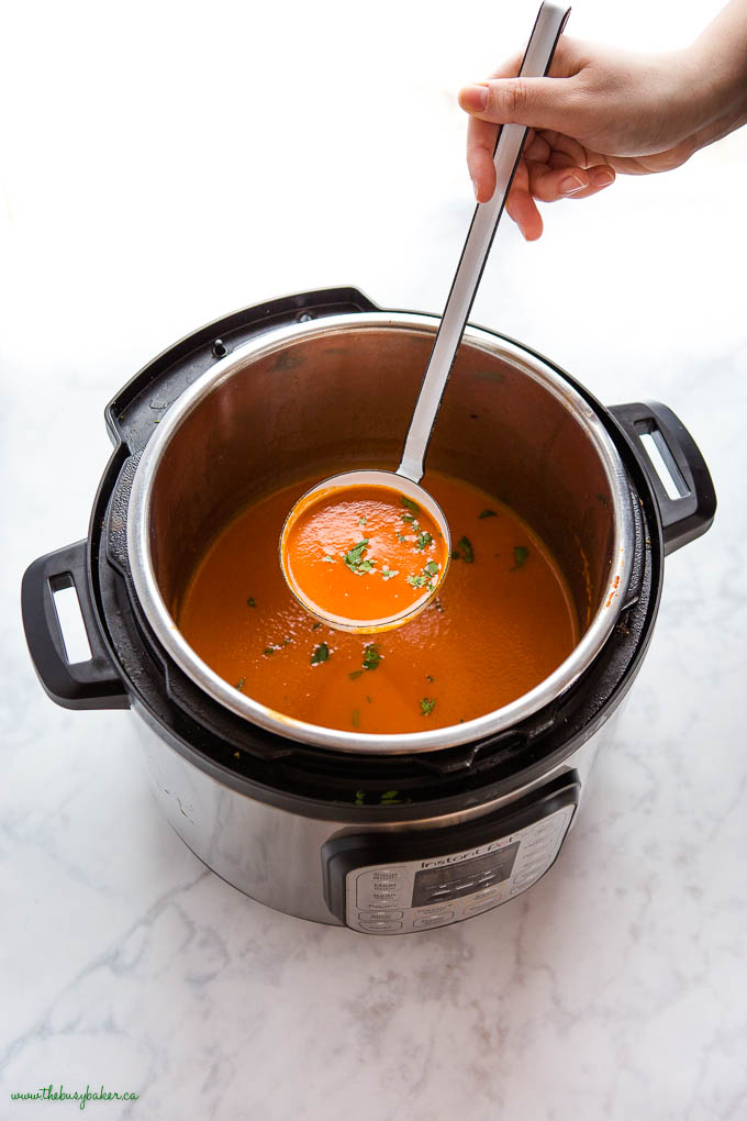 hand holding ladle of Instant Pot Tomato Soup