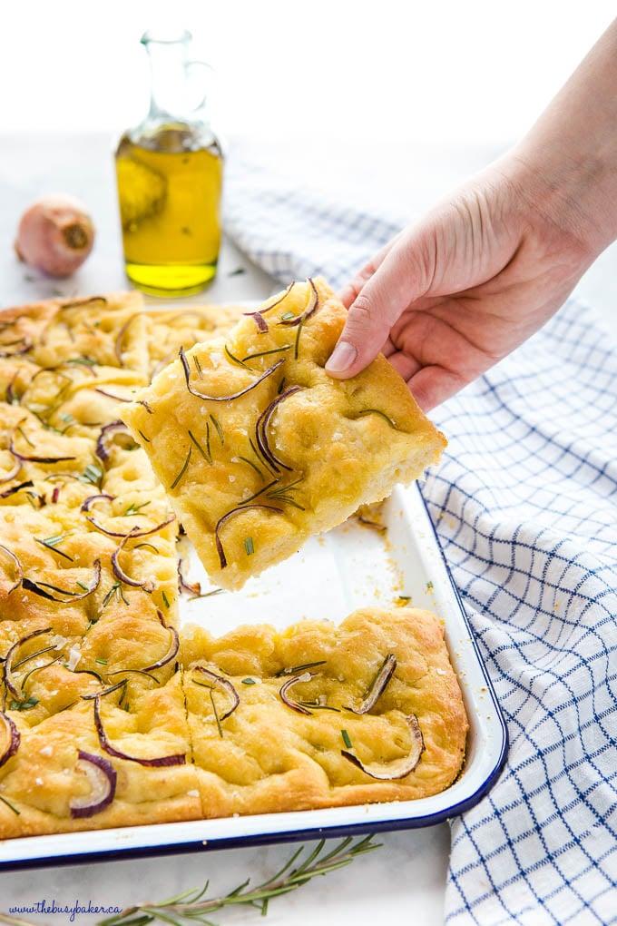 hand holding slice of rosemary onion focaccia bread
