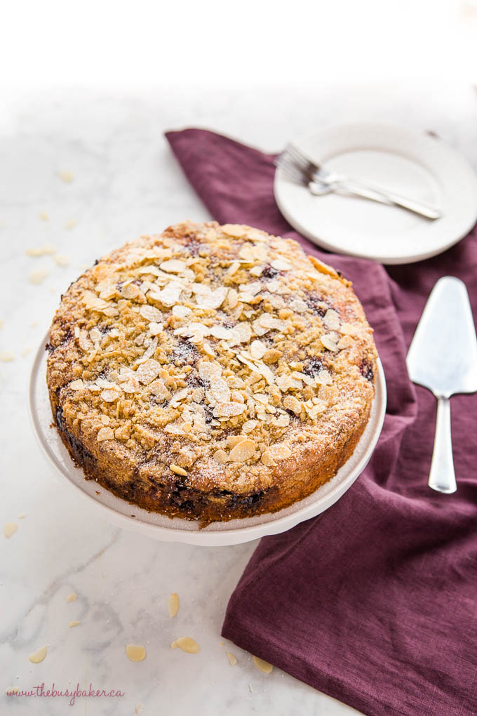 cherry almond coffee cake with sliced almonds on cake stand