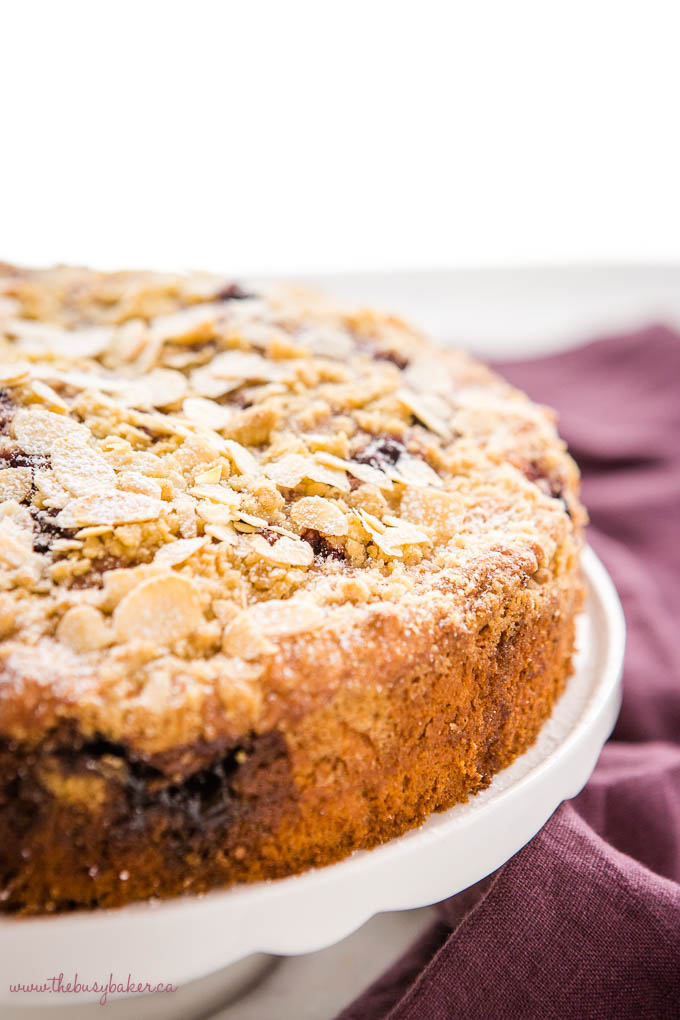 cherry almond coffee cake on white cake stand with slivered almonds and powdered sugar