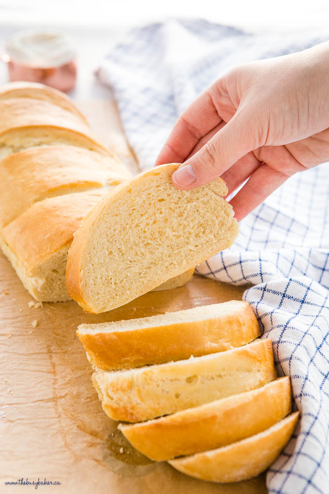 hand holding slice of homemade french bread