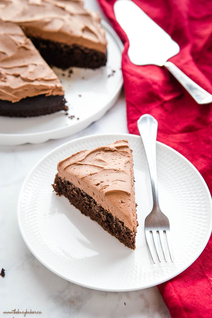 slice of chocolate cake with chocolate frosting on a white plate with a fork