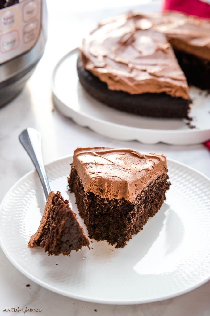 slice of instant pot chocolate cake with frosting on a white plate