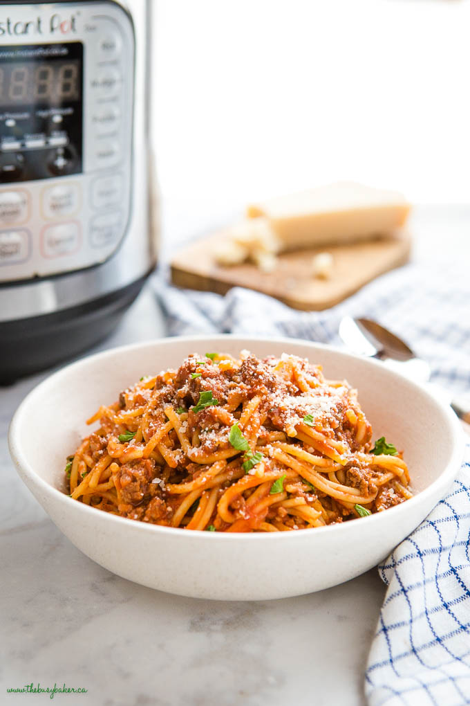 bowl of spaghetti and meat sauce with parmesan cheese, and the Instant Pot in the background