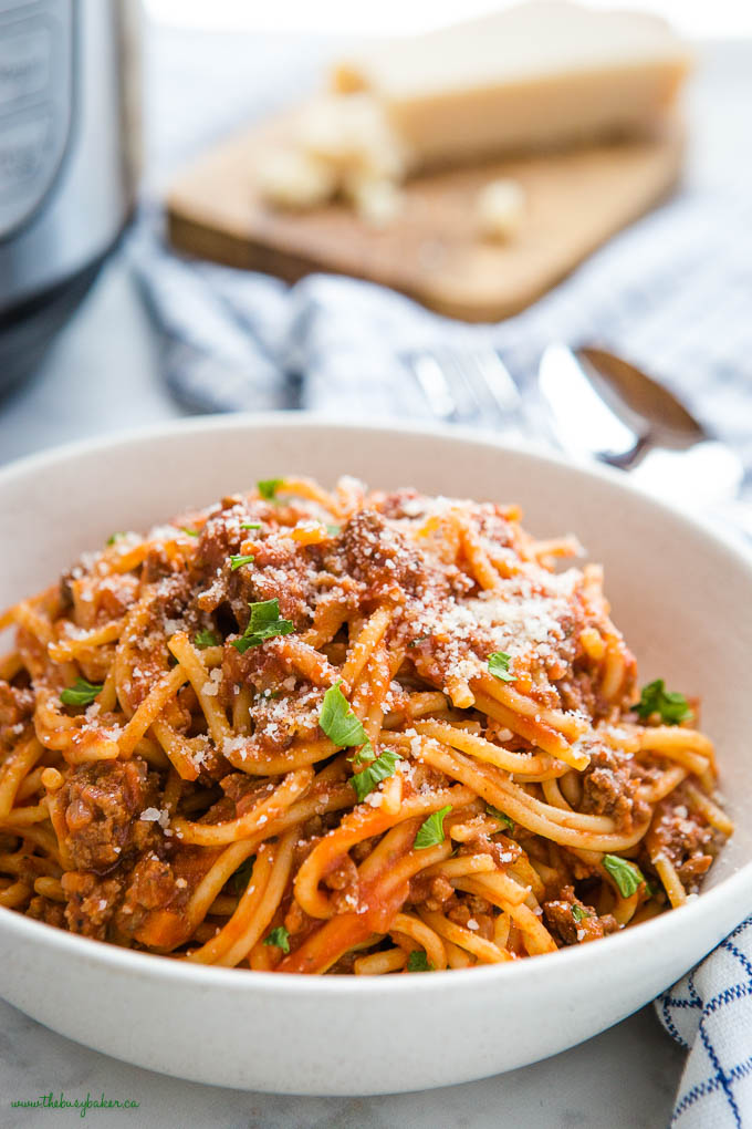 closeup image of spaghetti and meat sauce with fresh herbs and parmesan cheese