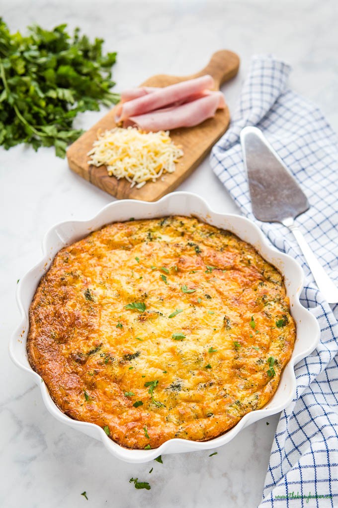 crustless quiche in white pie dish with ham and cheese and herbs