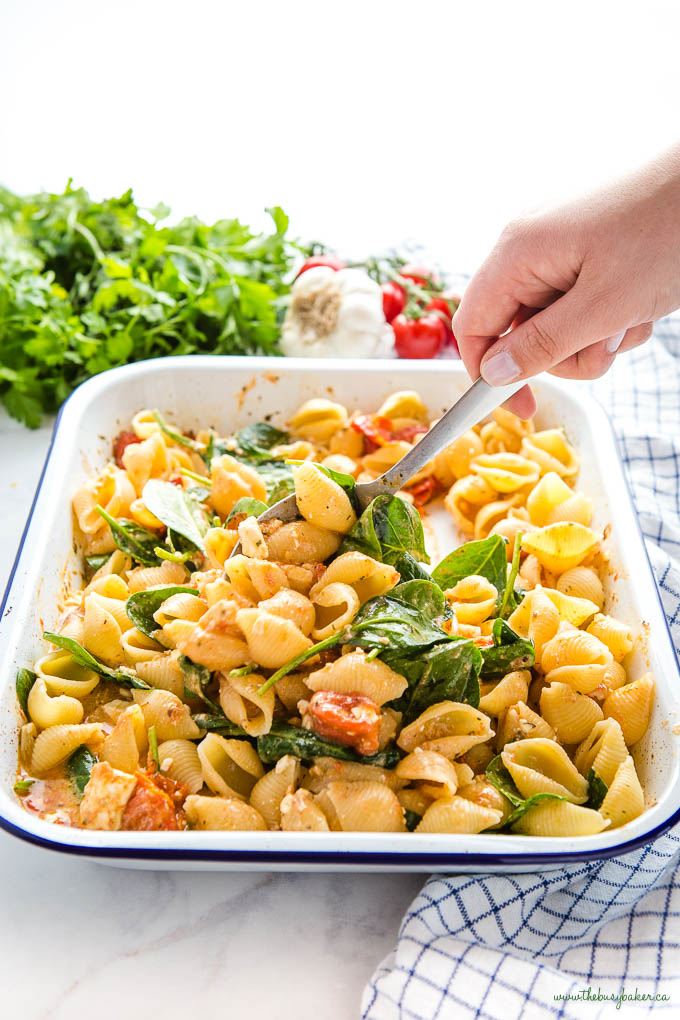 hand serving baked feta pasta with tomatoes and spinach