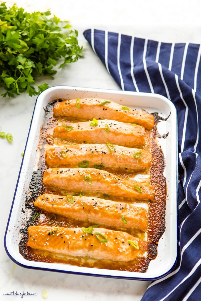 miso salmon on white baking tray with green onions and sesame seeds