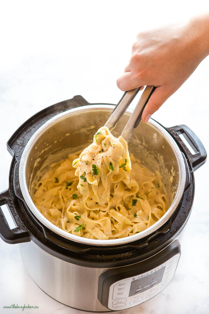 hand serving Fettuccine Alfredo from the Instant Pot