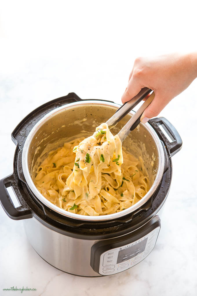 hand serving Instant Pot Fettuccine Alfredo from the Instant Pot